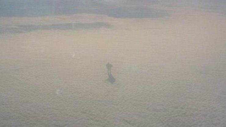Muž vyfotil z letadla postavu chodící v mracích. Jaké má tato záhadná fotka vysvětlení?